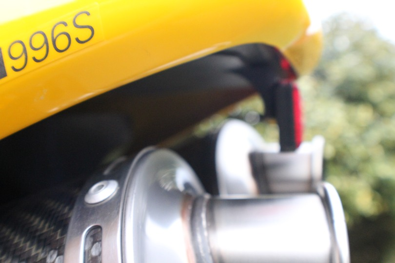 Across the top of the exhausts.